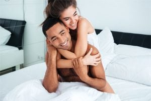 Happy couple hugging in bedroom